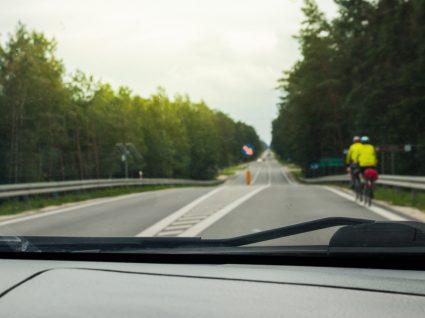 condutor prestes a pisar linha contínua para ultrapassar ciclistas