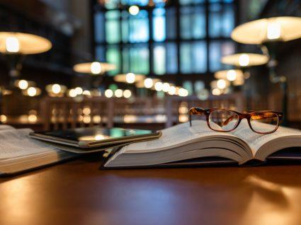livros e óculos pousados em cima de uma mesa na biblioteca