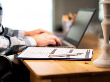 pessoa ao computador com contrato para suspender o estágio assinado