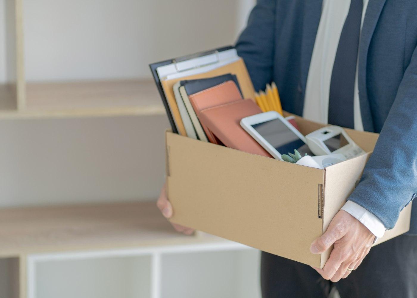 pessoa a segurar caixas com coisas do escritório depois de suspender o estágio