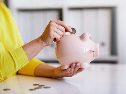 mulher aplica regra 50 30 20 ao colocar dinheiro no mealheiro
