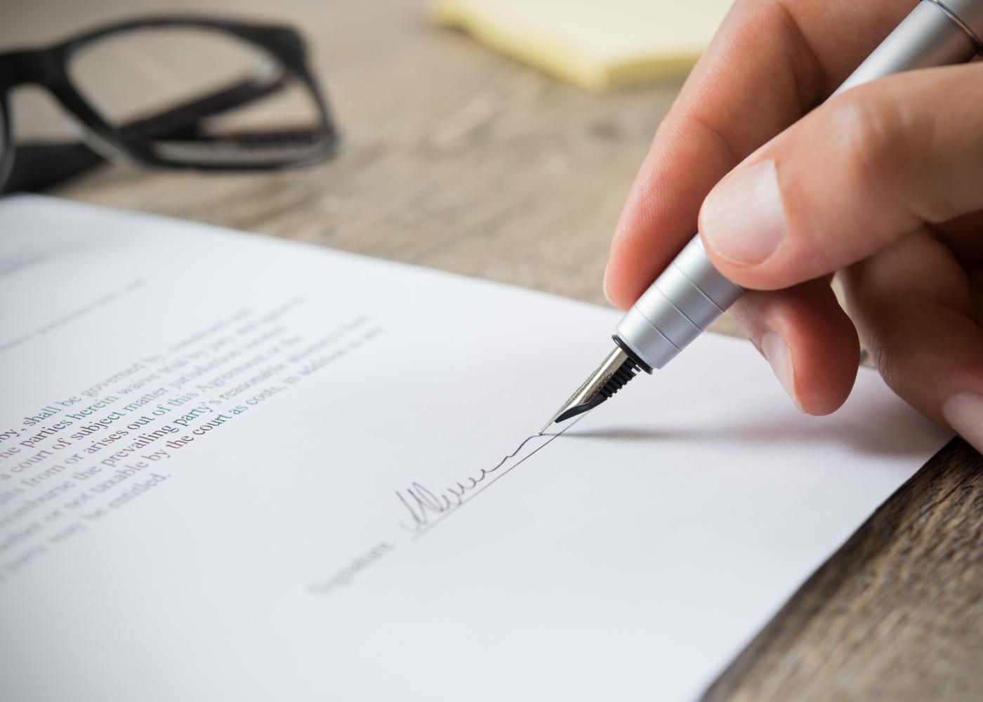 Homem a assinar contrato de mútuo