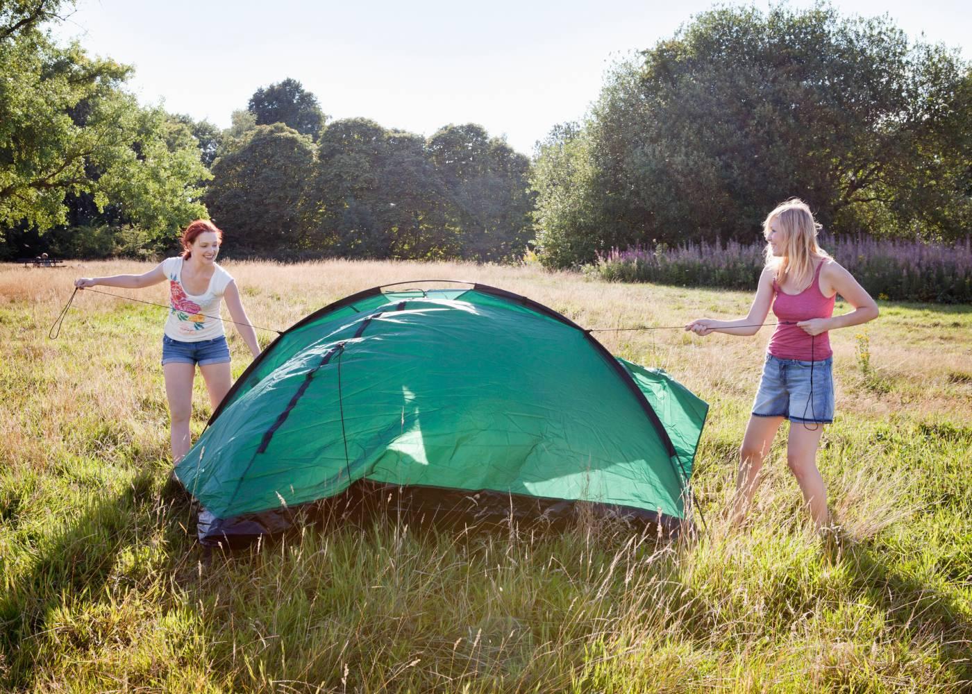 Raparigas jovens a montar tenda de campismo