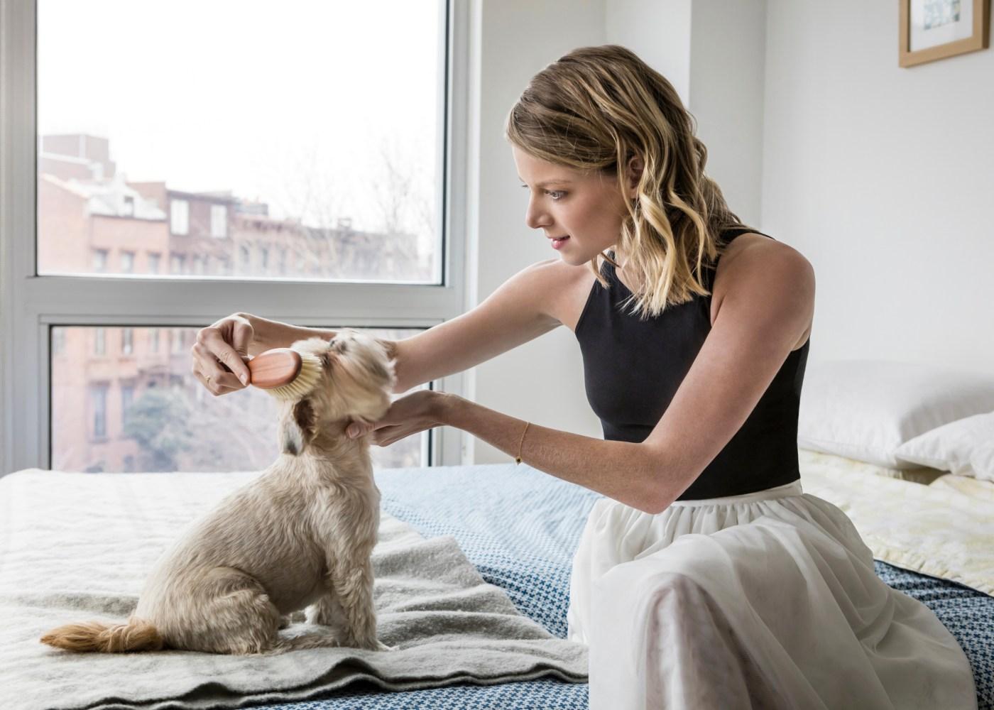 Mulher a pentear cão