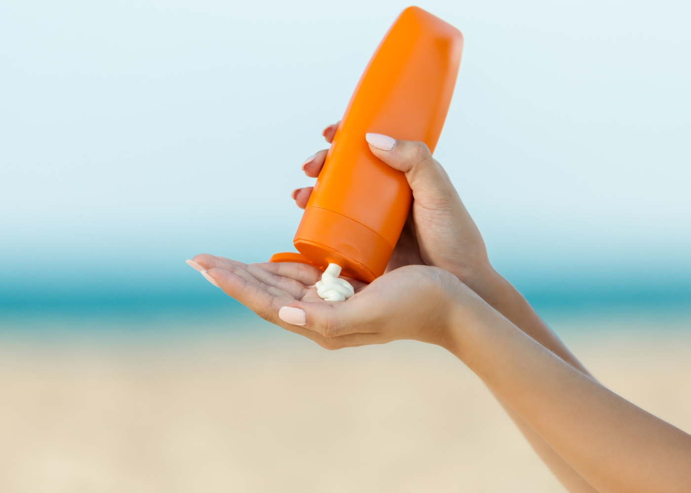 mulher a colocar protetor solar na mão