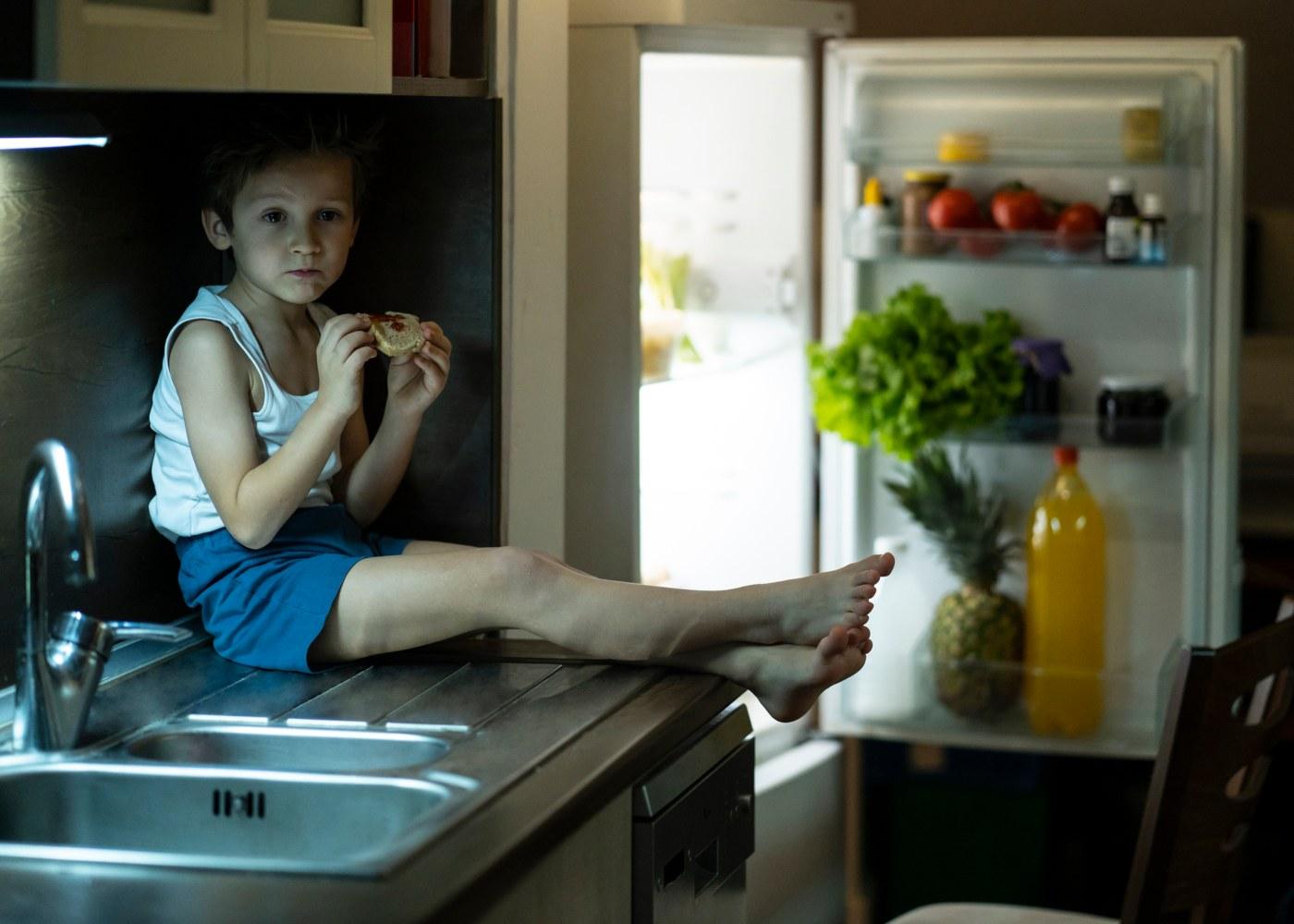 Criança a comer junto ao frigorífico
