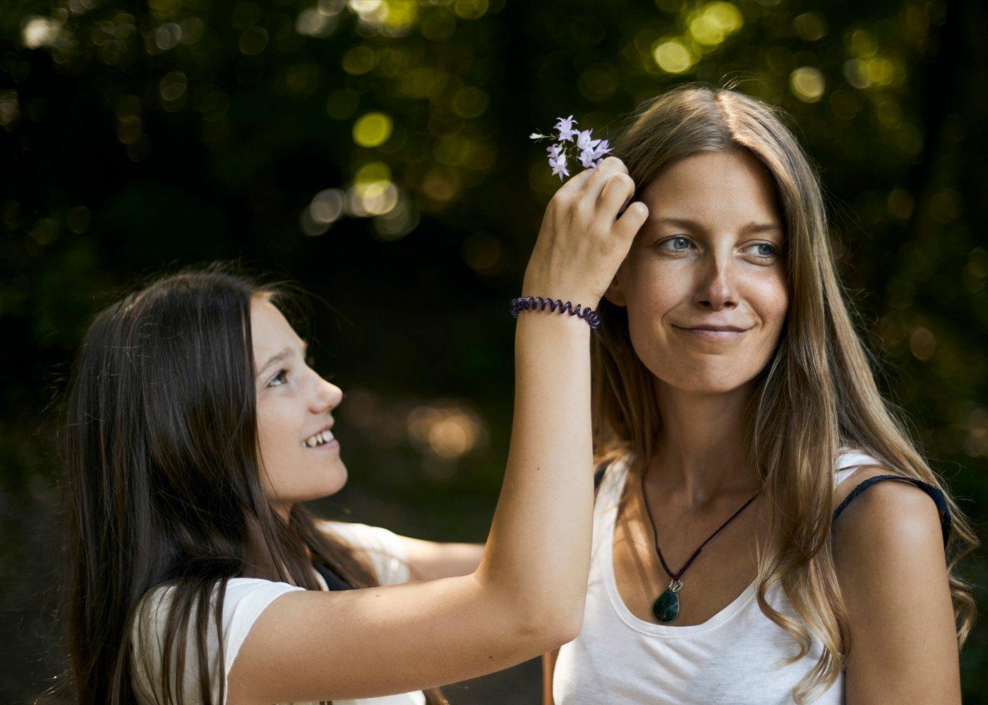Filha a enfeitar o cabelo da mãe com flores
