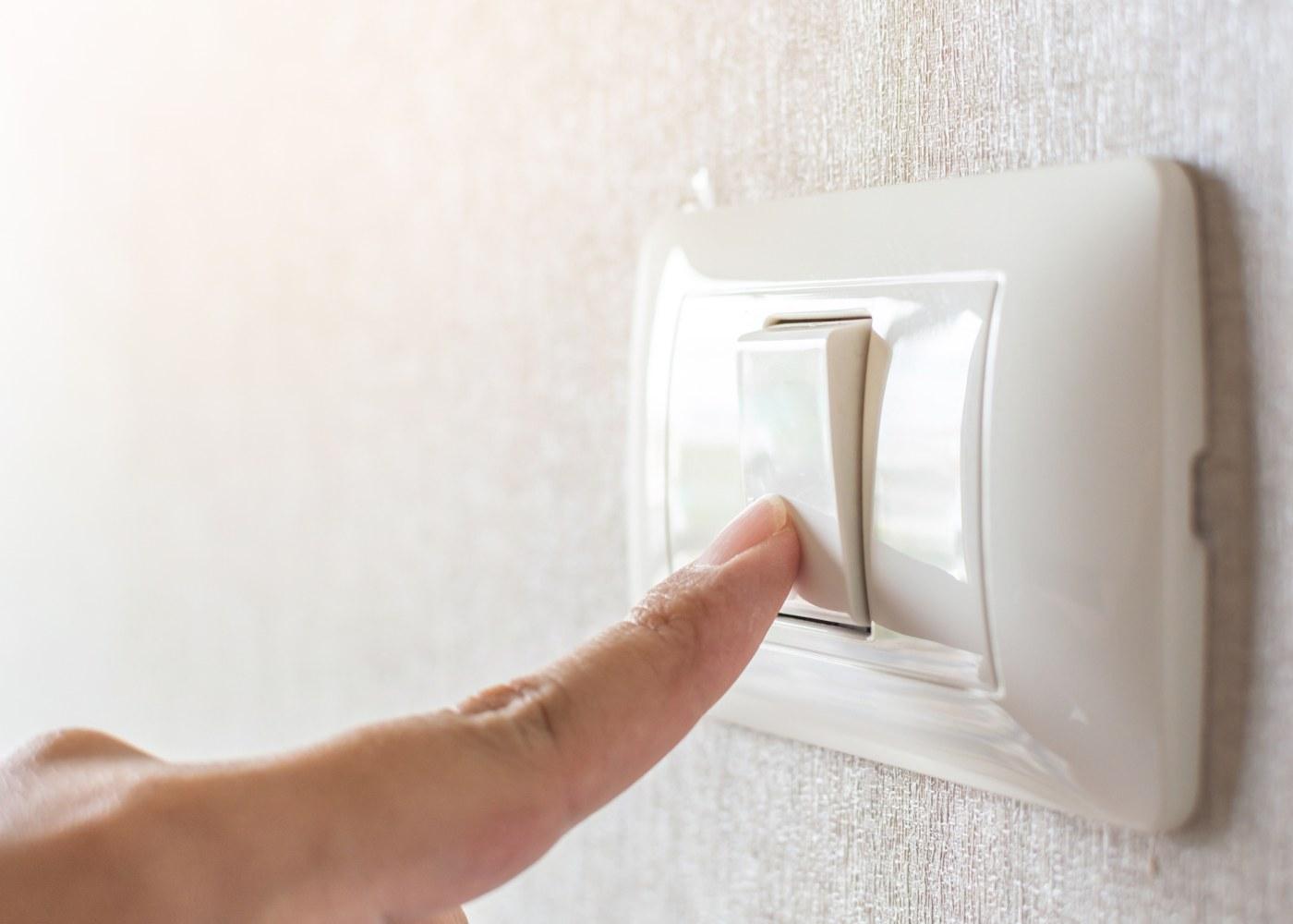 mão a desligar o interruptor da luz