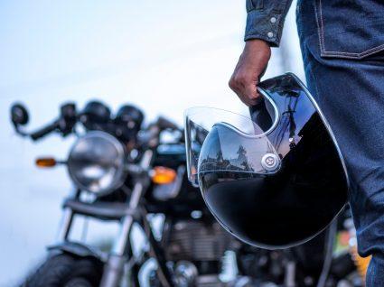 Homem com capacete de mota na mão