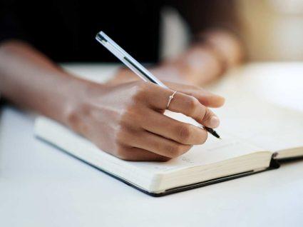 mulher anota despesas no seu livro kakebo