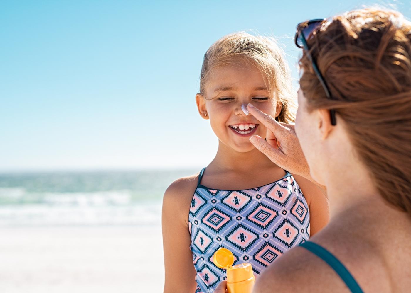 mãe a colocar protetor solar no rosto de criança