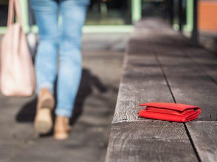 mulher acaba de perder a carteira ao deixá-la num banco de jardim