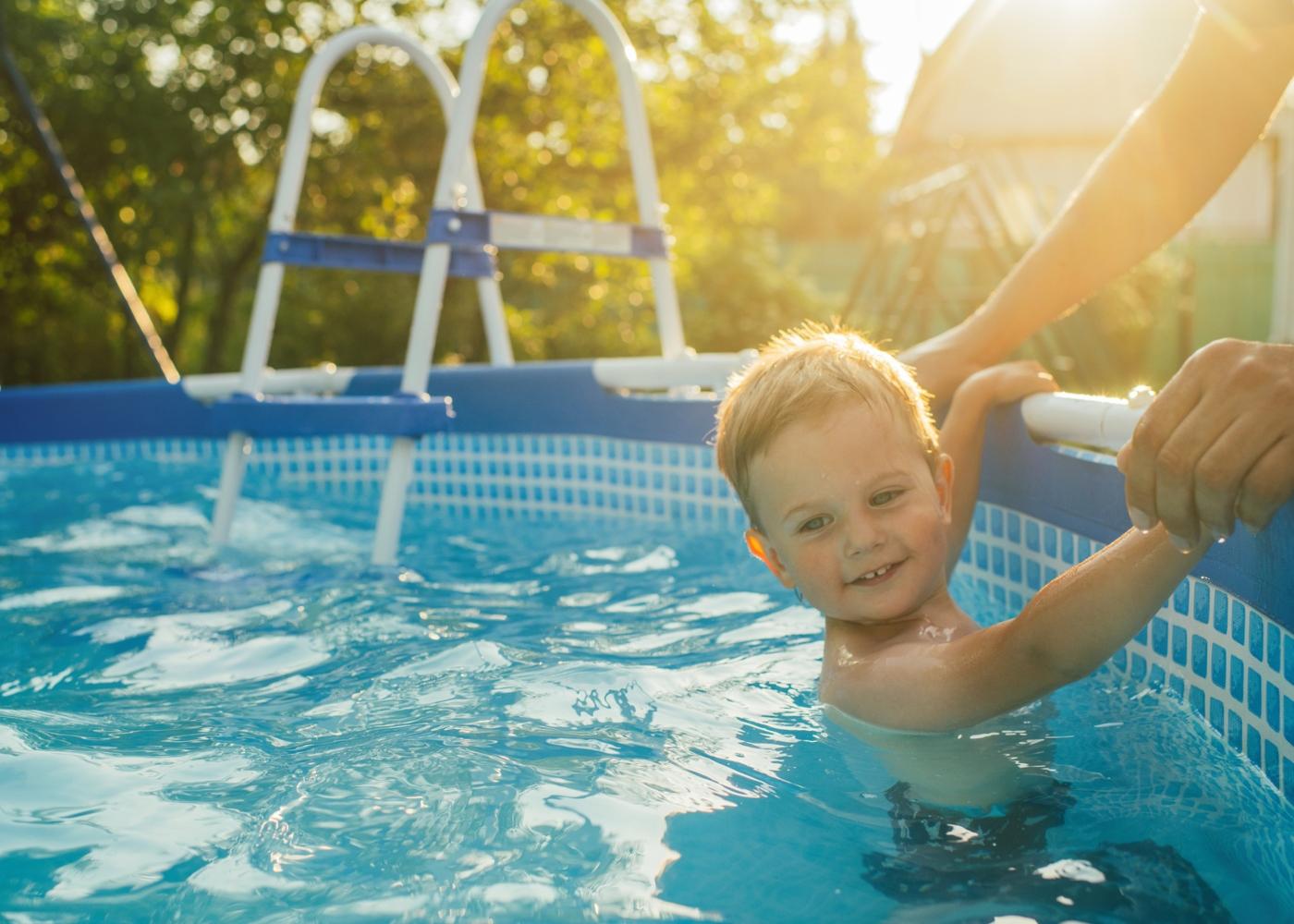Menino a divertir-se numa piscina desmontável