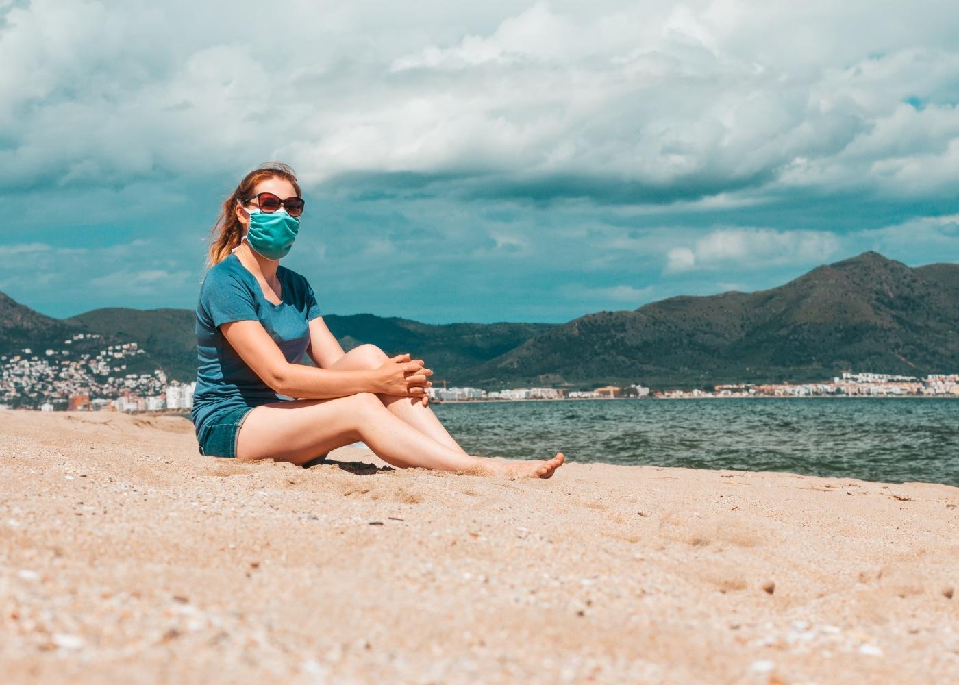 mulher com máscara sentada no areal