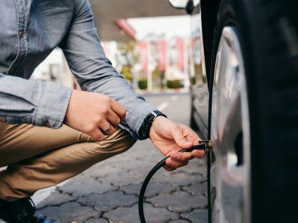 homem a verificar ar dos pneus e preparar o carro para viajar