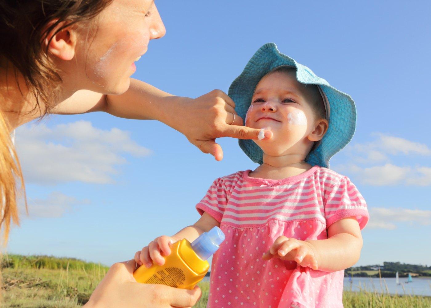 Mãe a colocar protetor solar em bebé