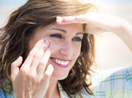 Mulher a aplicar protetor solar para o rosto