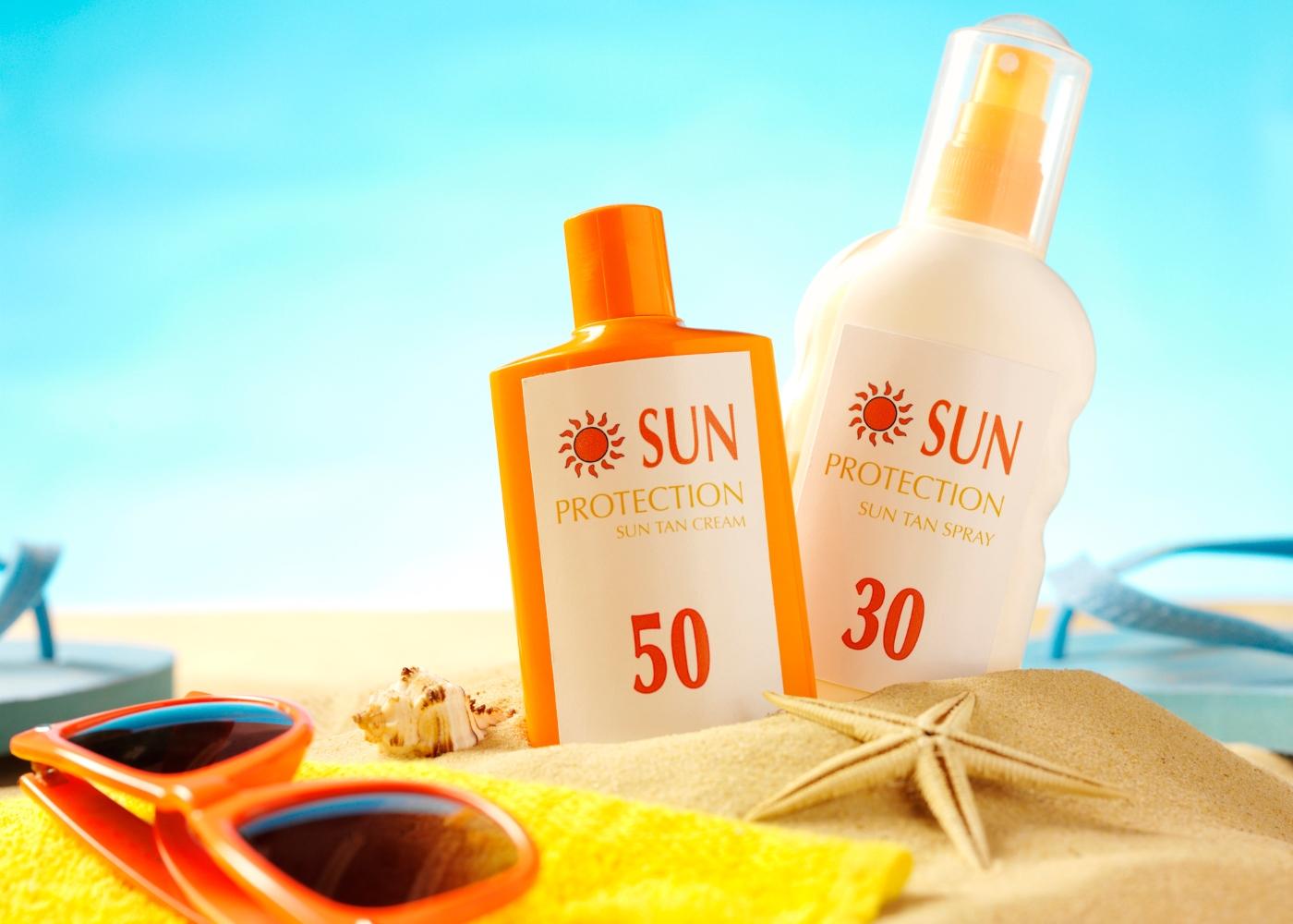 protetores solar na toalha de praia