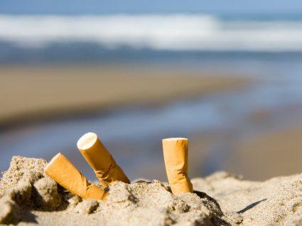Beatas de cigarro na areia da praia