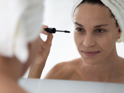 mulher aplica máscara de pestanas à prova de água