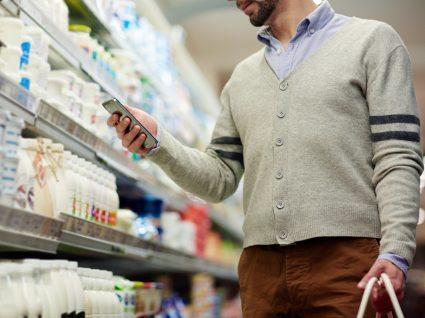homem compara o preço por quilo de diferentes embalagens usando a calculadora do telemóvel