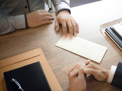 patrão a entregar a funcionário documentos de rescisão por mútuo acordo em layoff