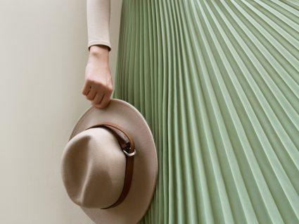 mulher usa saia plissada com chapéu