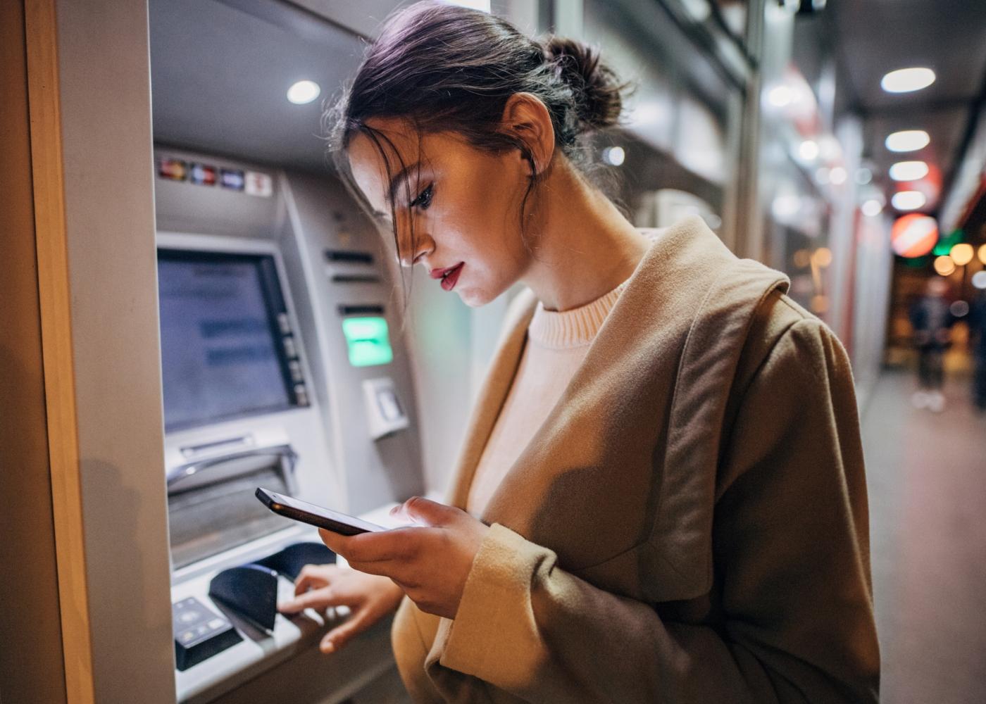 Mulher a fazer transferência bancária numa caixa Multibanco