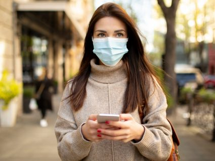 Mulher com máscara a utilizar a app StayAway Covid