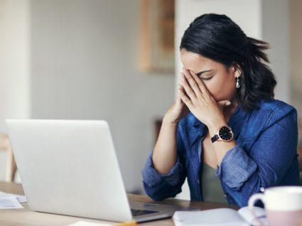 mulher ao computador com mãos na cara de cansaço