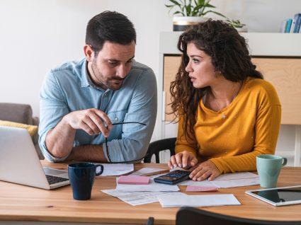 Casal a fazer contas e a analisar o orçamento familiar