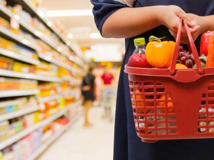 mulher segura cesto de supermercado enquanto põe em prática conselhos de poupança