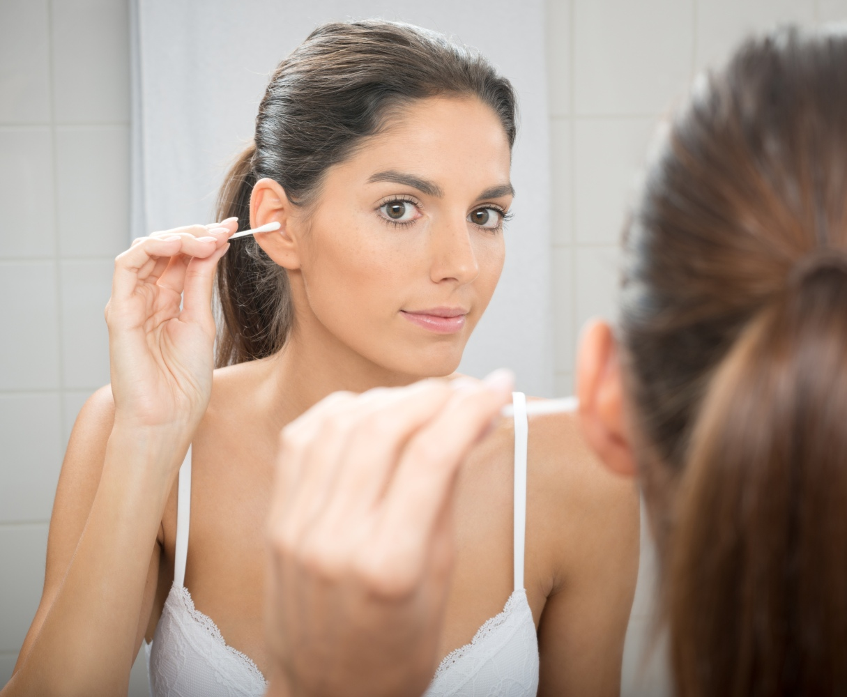 Mulher a limpar os ouvidos com cotonete