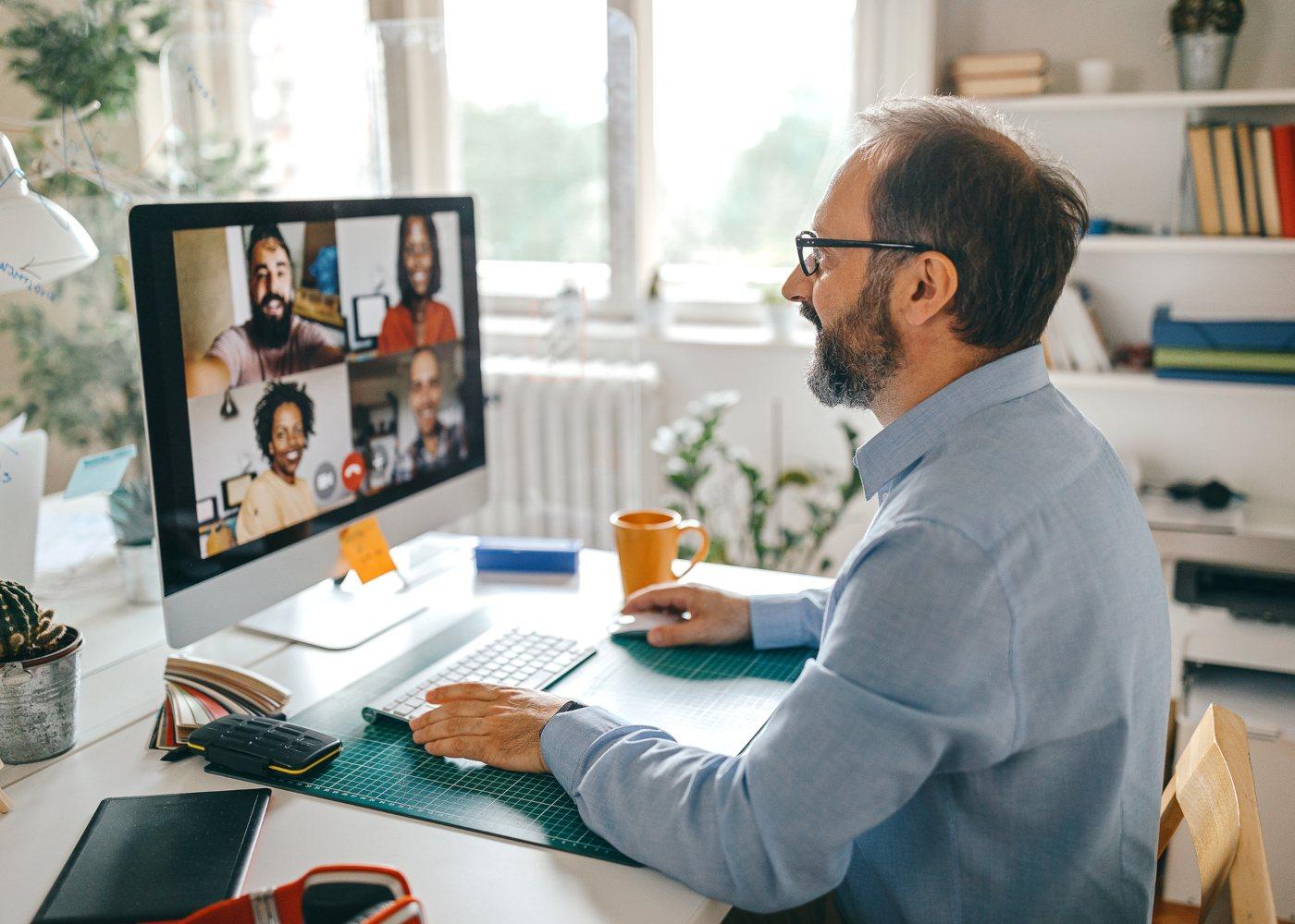 trabalhador em reunião online com equipa depois de consultar livro verde