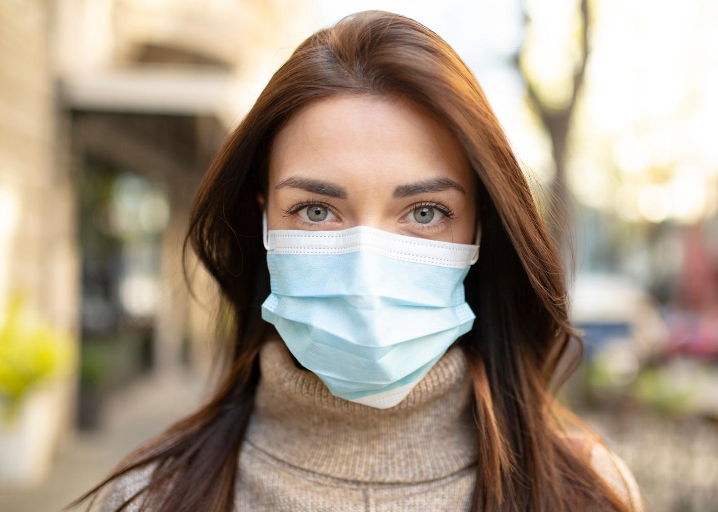 Mulher com máscara de proteção na via pública