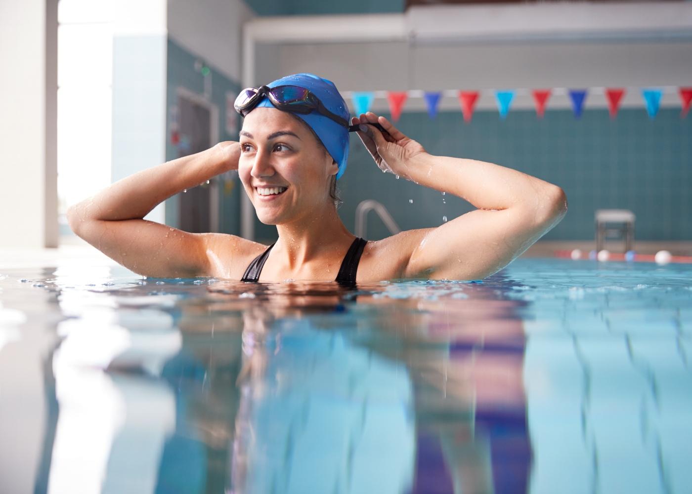mulher com touca e óculos em piscina