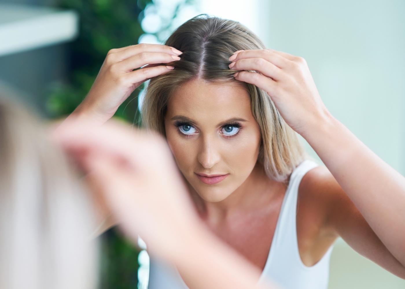 Mulher a inspecionar o cabelo ao espelho