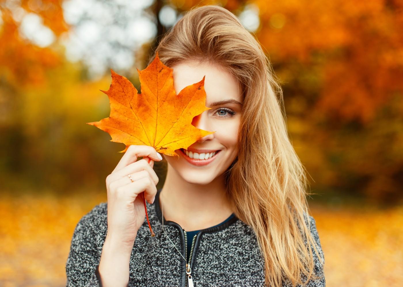 Mulher com folha caída no outono