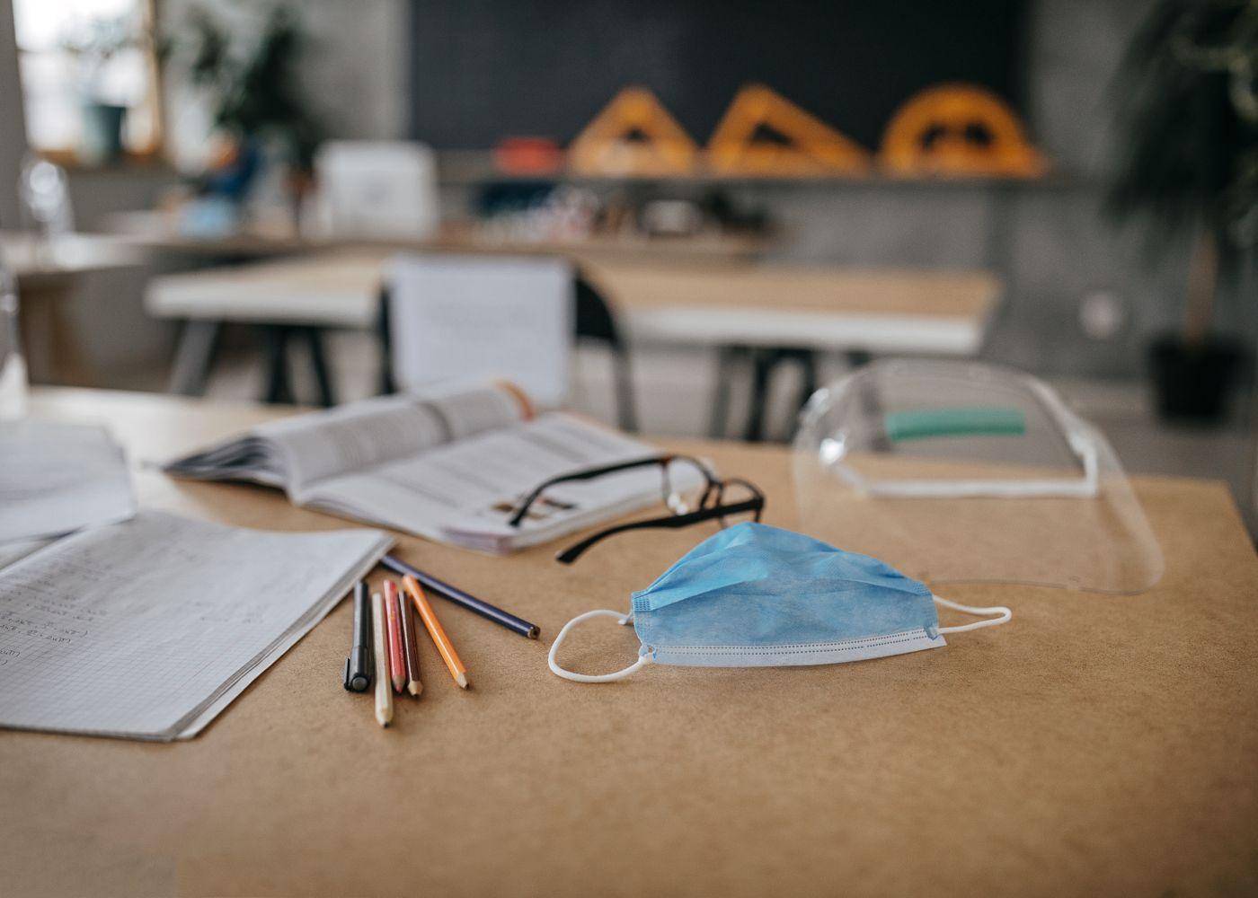 mesa de escola com livros, lápis e máscara de proteção