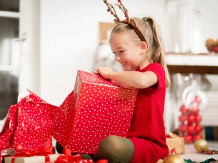 menina muito entusiasmada a abrir presente de natal