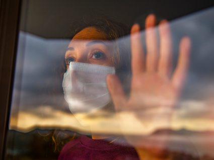 Mulher com máscara na janela de casa