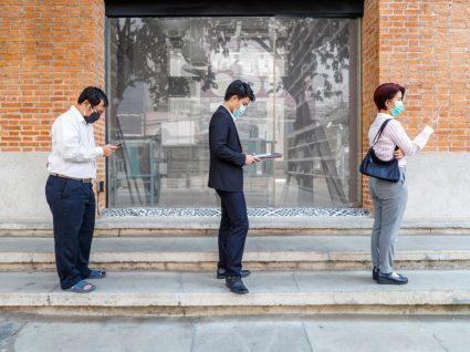 fila de pessoas com máscara na rua