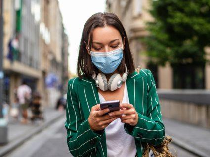 Mulher com máscara na rua a utilizar a app StayAway Covid