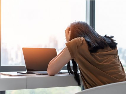 mulher a trabalhar e a mostrar cansaço com mãos na cabeça