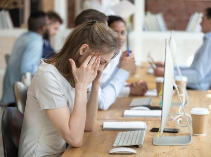 mulher em frente ao computador no escritório com mãos na cabeça em agonia