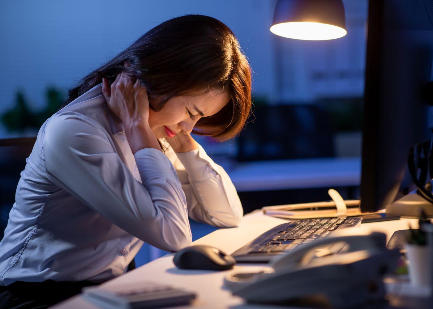 mulher com sinais de sofrimento a trabalhar