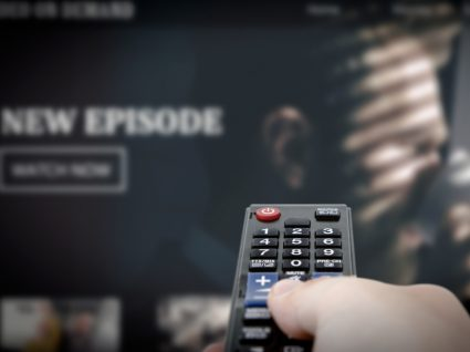 Homem a ver série da Netflix em casa