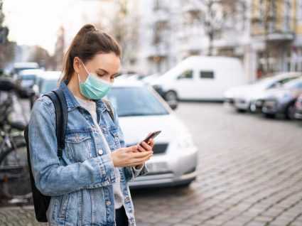 Mulher com máscara na rua à procura da farmácia mais próxima na app Farmácias