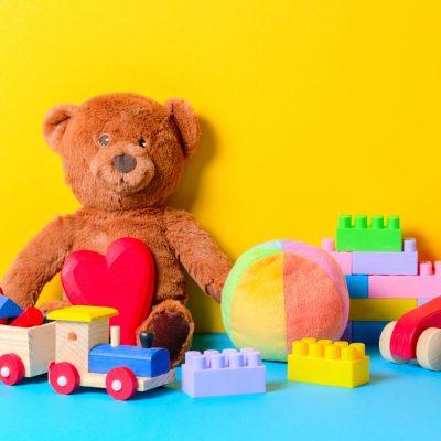 urso de peluche, legos, bola e carrinhos de madeira