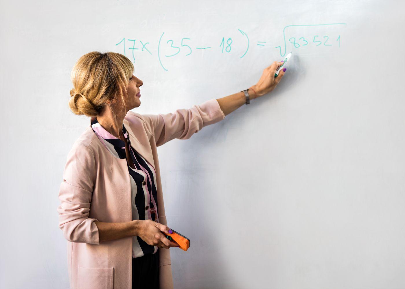 professora de matemática a escrever equação no quadro